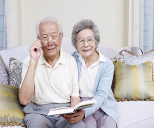 senior asian couple reading a book together at home.